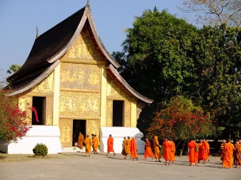 Monges visitando templo em Luang Prabang